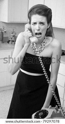 Young Caucasian woman in a kitchen weeps while on the phone - stock photo