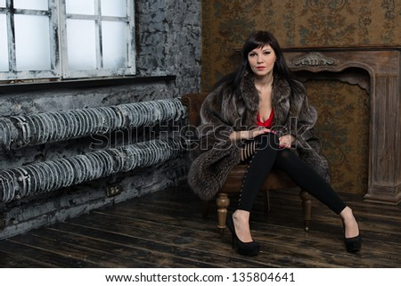 Young caucasian woman in a vintage interior wearing fur coat - stock photo