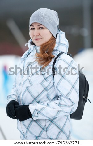 Young Caucasian woman in a winter jacket with black backpack walking at wintry weather