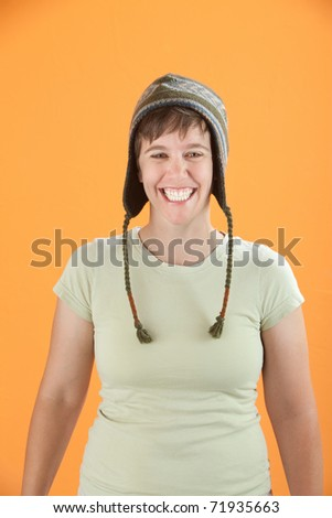 Young Caucasian woman in cap grinning from ear to ear