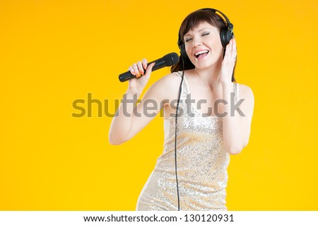 Young caucasian woman in headphones singing with a microphone - stock photo