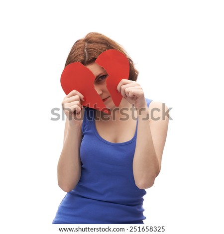 Young caucasian woman in her twenties holding two halves of a torn apart red heart isolated over the white background