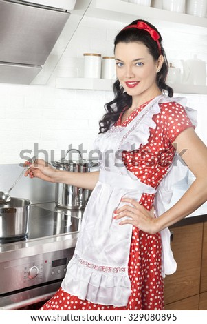 Young Caucasian woman in kitchen on a stove cooking soup - stock photo