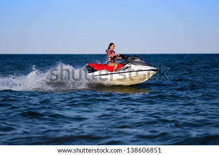 Young caucasian woman in life jacket on a wave runner  - stock photo