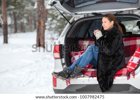 Young Caucasian woman in mink fur sitting in car trunk and drinking hot tea. Walking in winter forest
