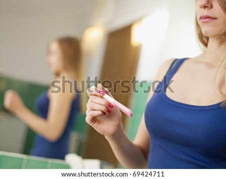 young caucasian woman in tanktop holding pregnancy test, waiting for results. Horizontal shape, cropped view