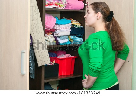 Young caucasian woman in the wardrobe selecting things for wear. - stock photo