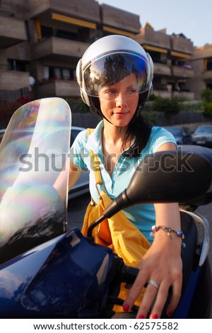 young caucasian woman is driving on the scooter - stock photo