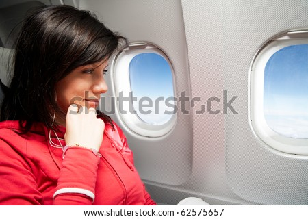 young caucasian woman is sitting in the airplane and dreaming - stock photo