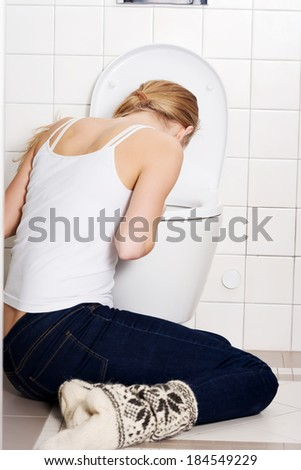 Young caucasian woman is vomiting in the bathroom. Bulimia, sick concept. - stock photo