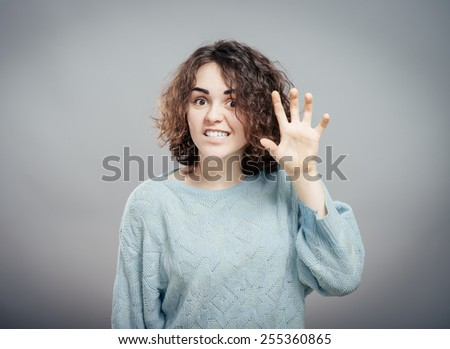Young Caucasian woman jokingly scare someone  - stock photo