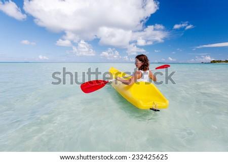 Young caucasian woman kayaking in sea at Maldives  - stock photo