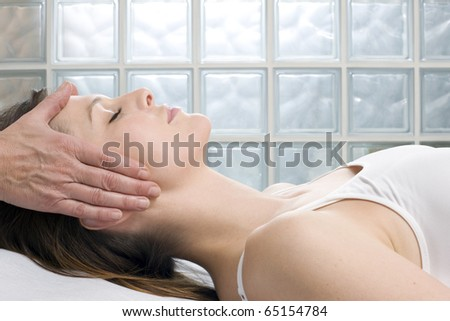 young caucasian woman lying down receiving head massage - stock photo