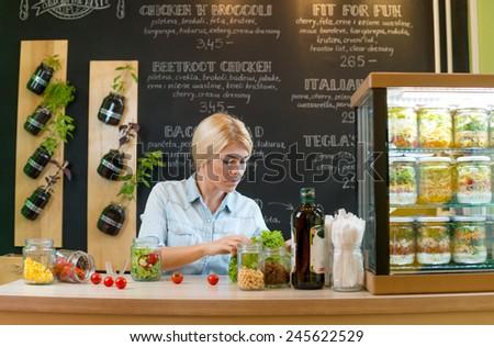 Young caucasian woman making salad - stock photo