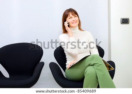 young caucasian woman on the mobile sitting in the waiting room for doctors - stock photo