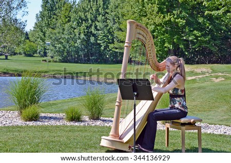 young Caucasian woman playing a harp by rural pond - stock photo