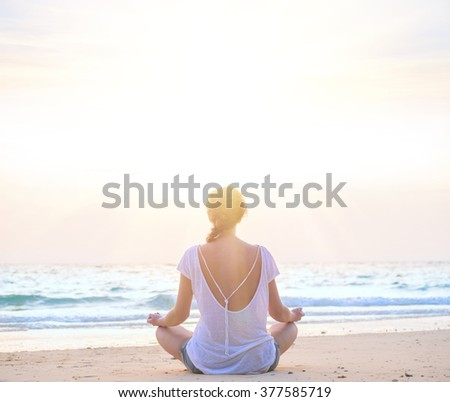 young caucasian woman practicing yoga at sunrise beach - stock photo