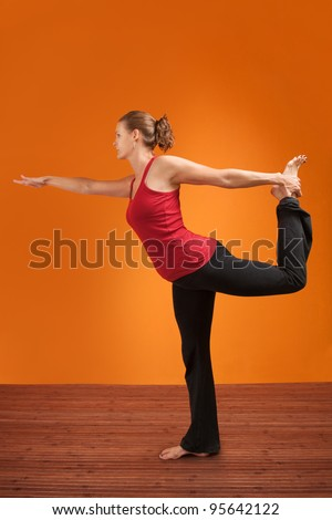 Young Caucasian woman practicing yoga stretches her leg - stock photo