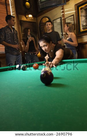 Young caucasian woman preparing to hit pool ball while playing billiards. - stock photo