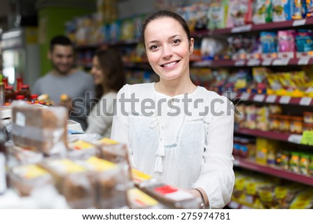 Young caucasian woman purchasing food for week at supermarket - stock photo