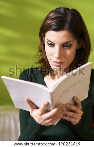 young caucasian woman reading book at home, sitting on sofa - stock photo
