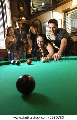 Young caucasian woman receiving advice on shooting pool ball while playing billiards. - stock photo