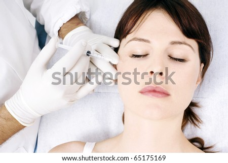 young caucasian woman receiving an injection from a doctor - stock photo
