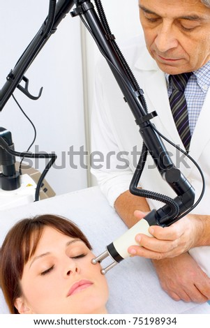 young caucasian woman receiving electrostimulation lifting from a male doctor - stock photo