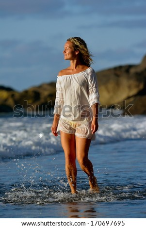 young caucasian woman refreshing on summer evening on the beach