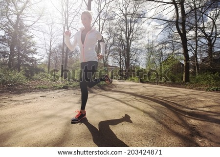Young caucasian woman running outdoors in forest on a sunny day. Fit female athlete jogging in a park. Caucasian female model training outdoors. - stock photo