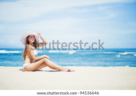 Young caucasian woman sitting on the beach, bali