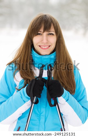 Young caucasian woman skiing at winter outdoor. Pretty smiling girl standing with ski - stock photo