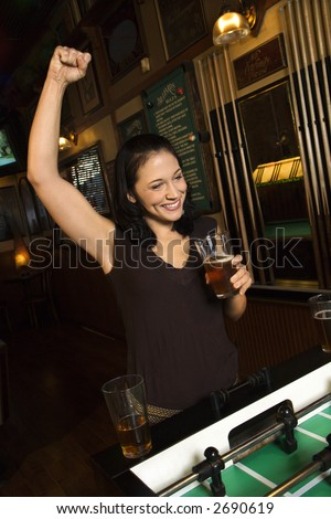 Young Caucasian woman smiling and cheering on foosball game. - stock photo