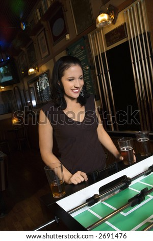 Young Caucasian woman smiling and watching foosball game. - stock photo