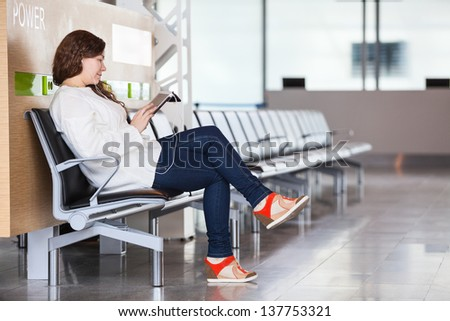 Young Caucasian woman spending time in airport lounge - stock photo