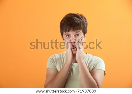 Young Caucasian woman squeezing her cheeks with her hands - stock photo
