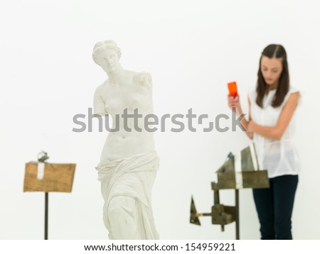 young caucasian woman standing and analyzing an artwork behind a replica of Venus de Milo in a museum - stock photo