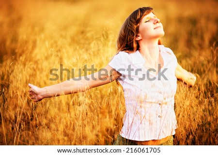 Young caucasian woman standing in dry grass field with raised arms in sunlight - stock photo