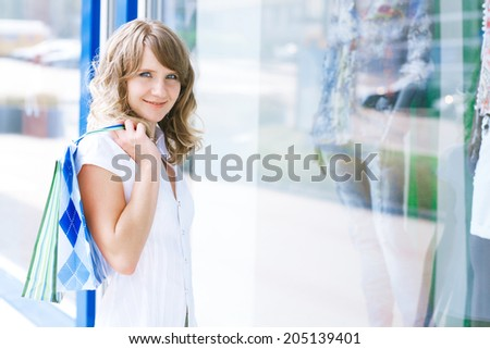 Young caucasian woman standing near a shop window with shopping bags.