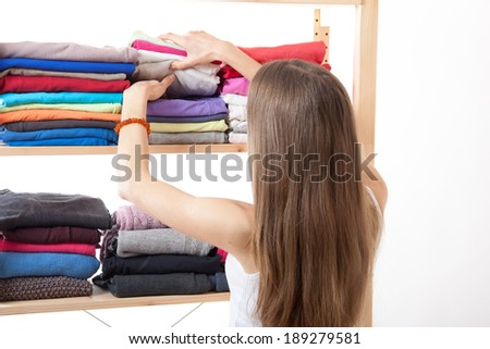 Young caucasian woman standing near the wardrobe - stock photo