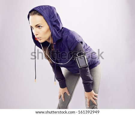 Young caucasian woman taking breath after jogging. Female athlete resting with hands on knees and looking away over grey background - stock photo