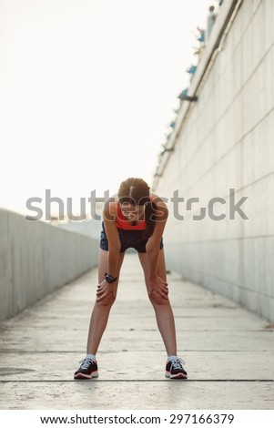 Young caucasian woman taking breath after jogging. Female athlete resting with hands on knees and looking down at sunset - stock photo