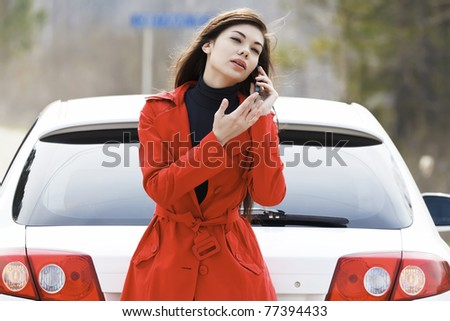Young caucasian woman talking by mobile telephone standing by her damaged car - stock photo