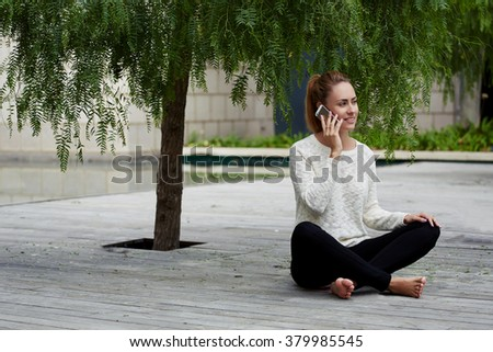 Young Caucasian woman talking on cell telephone while relaxing outside under deciduous tree on wooden pier, carefree female sitting outdoors and calling with mobile phone during autumn weekend in park - stock photo