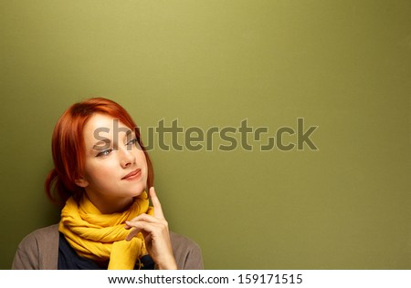 Young caucasian woman thinking near the green wall