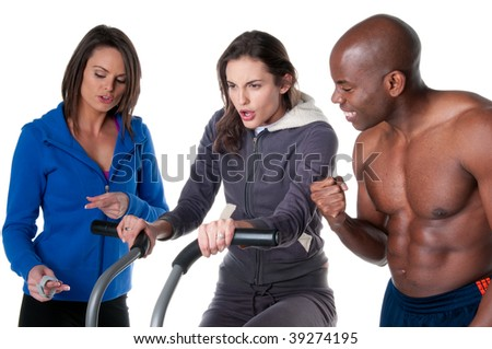 Young caucasian woman trainning in the gym with personal trainer and friend. - stock photo