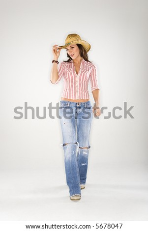 Young Caucasian woman walking to viewer and tilting cowboy hat. - stock photo