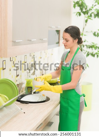 young caucasian woman washing dishes in the kitchen at home - stock photo