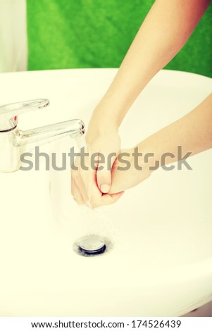 Young caucasian woman washing hands in bathroom.  - stock photo