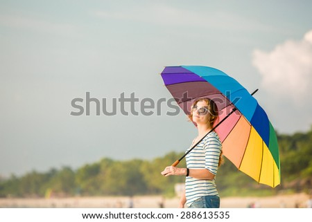 Young caucasian woman wearing white sunglasses with colourful rainbow umbrella looking at ocean on the Jimbaran beach on Bali before sunset. Travel, holidays, vacation, healthy lifestyle, tranquility